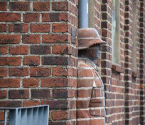 man hidden in bricks